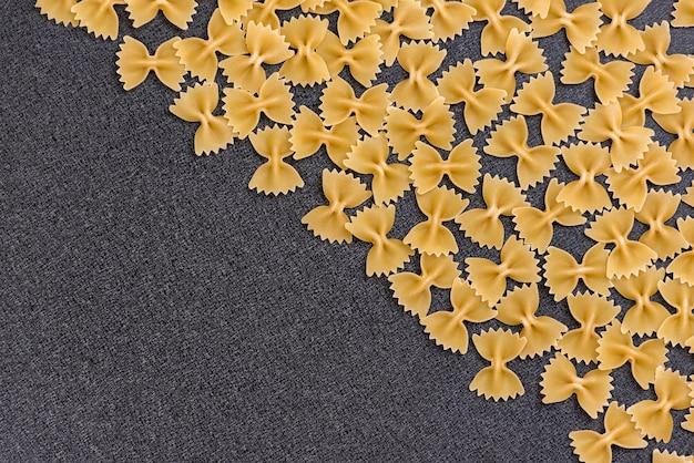 Farfalle oder fliege pasta auf schwarzem hintergrund. hintergrund kochen. italienische küche. speicherplatz kopieren. vorlage. attrappe, lehrmodell, simulation Premium Fotos