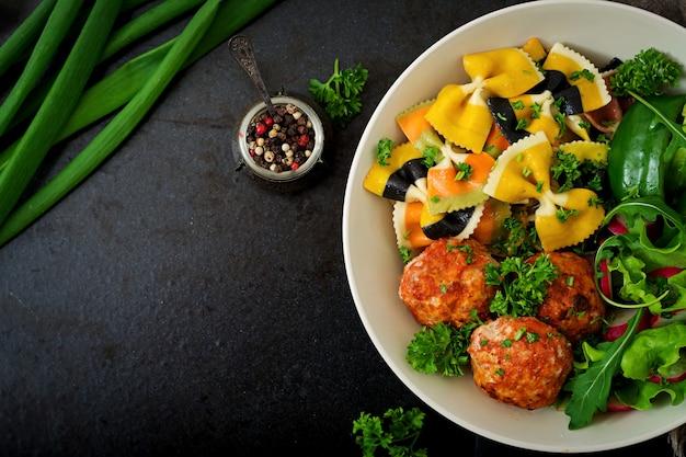 Farfalle pasta hartweizen mit gebackenen fleischbällchen aus hähnchenfilet in tomatensauce und salat in einer schüssel. Kostenlose Fotos