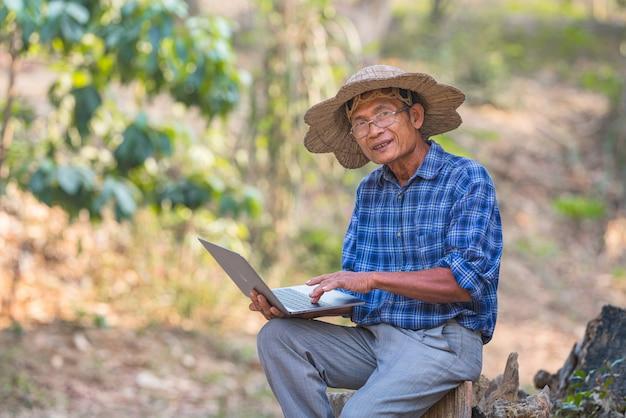 Farmer asian mit smartphone und laptop, business- und technologiekonzept Premium Fotos