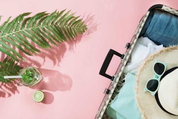 Farnblatt, tropisches detoxwasser und offener koffer mit kleidung auf pastellrosa. Premium Fotos