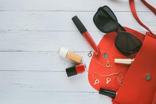 Fashion-konzept. rote handtasche, kosmetikprodukte, sonnenbrille, ohrringe. Premium Fotos