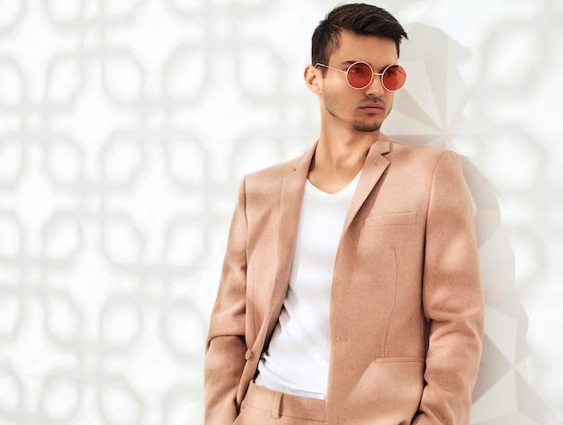 Fashion stilvolles modell in eleganten hellrosa anzug gekleidet Kostenlose Fotos