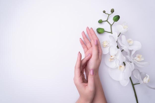 Fashionrt-porträtfrau blüht in ihrer hand mit einem hellen kontrastierenden make-up. Premium Fotos