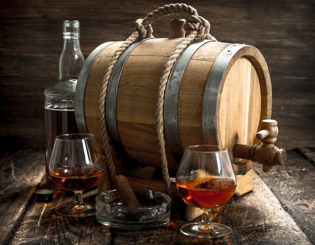 Fass mit französischem cognac, gläsern und einer zigarre Premium Fotos