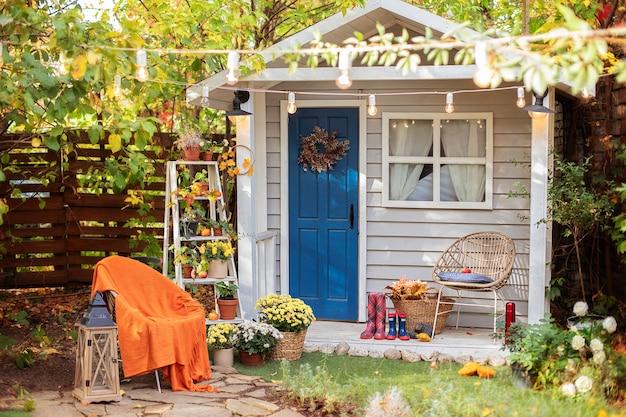 Fassade herbst gemütliches haus mit veranda mit stuhl, decke, chrysanthemen. Premium Fotos