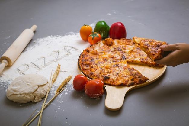 Fassen sie die pizza ab, die auf mehl mit einer geschmackvollen pizza geschrieben wird Kostenlose Fotos