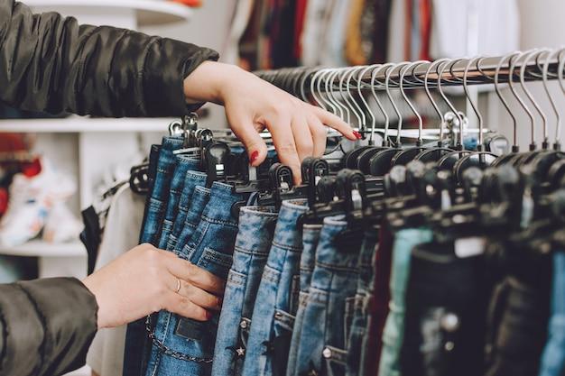 Fast-fashion-konzept. frau wählt jeans in einem geschäft Premium Fotos