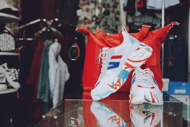 Fast-fashion-konzept. rote handtasche und schuhe auf regal im shop, speicher. Premium Fotos