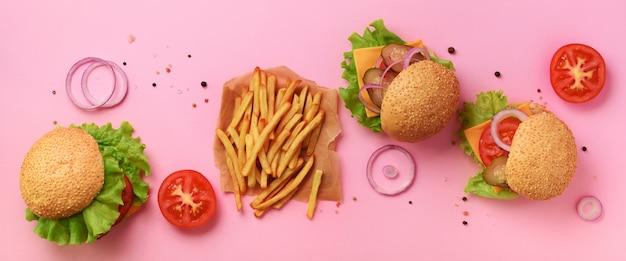 Fast-food-banner. saftige fleischburger mit rindfleisch, tomate, käse, zwiebel, gurke und kopfsalat auf rosa hintergrund. Premium Fotos