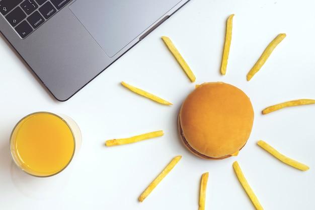 Fast food bei der arbeit snacks. laptop, hamburger und pommes frites am arbeitsplatz. Premium Fotos