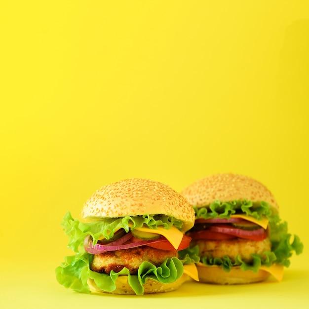Fast-food-konzept. quadratische ernte. saftige selbst gemachte hamburger auf gelbem hintergrund. essen zum mitnehmen. rahmen für ungesunde ernährung Premium Fotos