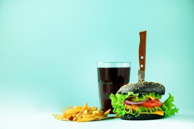 Fast-food-konzept. saftige selbst gemachte hamburger auf blauem hintergrund. essen zum mitnehmen. rahmen der ungesunden diät mit kopienraum Premium Fotos