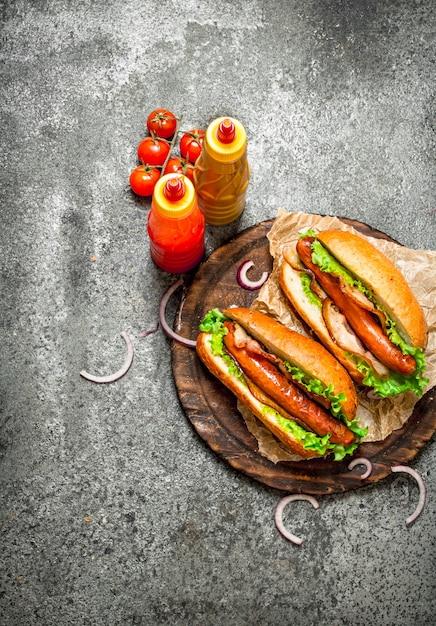 Fast-food-menü. hot dogs rindfleischgrill mit kräutern, ketchup und heißem senf auf rustikalem tisch. Premium Fotos