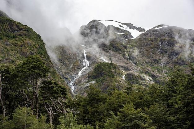 Faszinierende aussicht auf die felsigen berge mit einem wasserfall Kostenlose Fotos