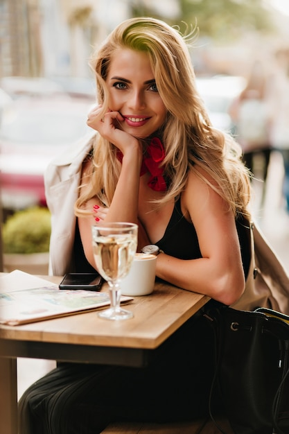 Faszinierende blondhaarige junge frau, die lächelt und im straßencafé mit tasse cappuccino sitzt. romantisches mädchen im schwarzen kleid mit ledertasche, die beim genießen des kaffees während des mittagessens aufwirft. Kostenlose Fotos