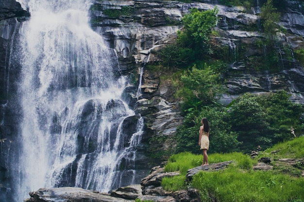 Faszinierende flachwinkelaufnahme einer frau, die den wasserfall im doi inthanon park in thailand bewundert Kostenlose Fotos