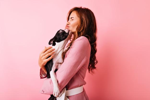Faszinierendes lockiges mädchen, das französische bulldogge küsst. porträt der glückseligen europäischen frau, die liebe zu ihrem hund ausdrückt. Kostenlose Fotos
