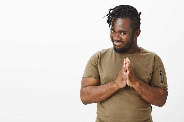 Faszinierter lustiger kerl in einem braunen t-shirt, das gegen die weiße wand aufwirft Kostenlose Fotos