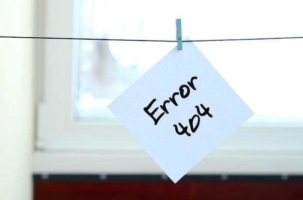 Fehler 404. hinweis wird auf einen weißen aufkleber geschrieben, der mit einer wäscheklammer an einem seil hängt Premium Fotos