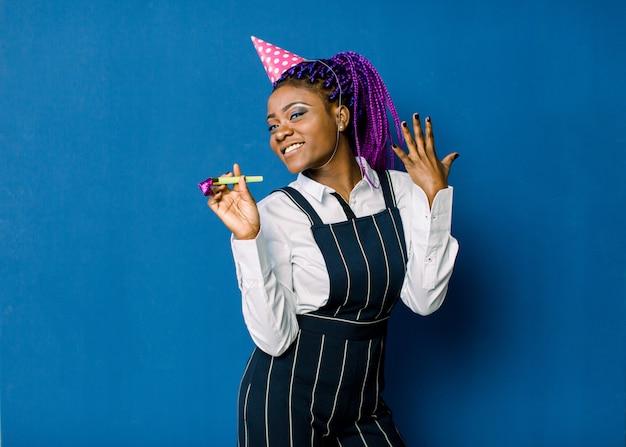 Feier, freunde, junggesellenabschied, geburtstagskonzept - lächelnde afroamerikanerin, die rosa parteihut trägt und gunsthorn bläst Premium Fotos