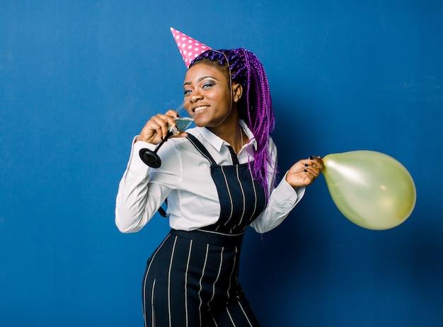 Feier-konzept, geburtstagsfeier - nahaufnahme porträt glückliche junge schöne afrikanische frau in schwarzen hosen und weißem rock lächelnd mit buntem gelbem partyballon. blue pastel studio. Premium Fotos