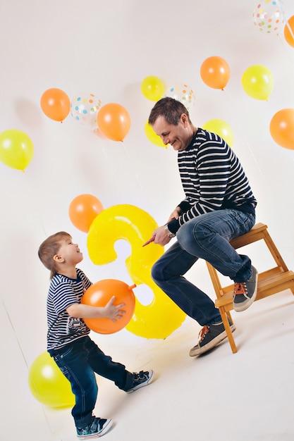 Feier, lustige zeit verbringen - familie auf der party. erwachsene und kinder auf einem weißen hintergrund unter den farbigen kugeln feiern ihren geburtstag Premium Fotos