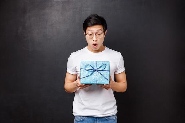 Feier, urlaub und lifestyle-konzept. überrascht und aufgeregt erhält ein erstaunter asiatischer typ eine geschenkbox, hält ein geschenk und schaut es amüsiert an. er hat nicht erwartet, dass sich ein mitarbeiter an den geburtstag erinnert Premium Fotos