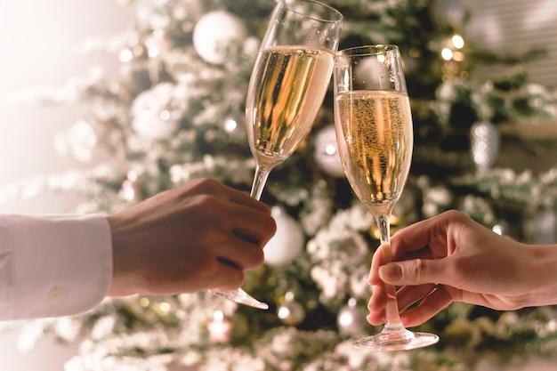 Feier weihnachten. paar, das gläser sekt hält Premium Fotos