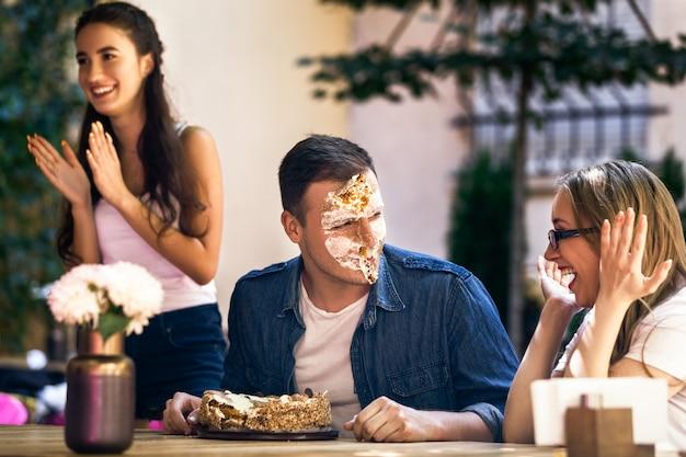 Feier zum geburtstag für einen erwachsenen jungen mit torte und gesichtsstreich Kostenlose Fotos