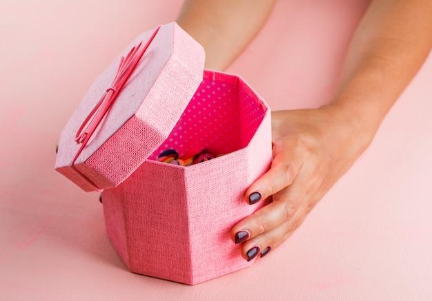 Feierkonzept auf der hohen winkelansicht des rosa tisches. frau öffnet geschenkbox. Kostenlose Fotos