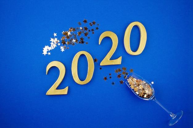 Feierkonzept des neuen jahres mit champagnerglas und konfettis über dem blauen hintergrund Premium Fotos