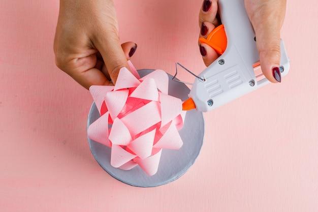 Feierkonzept mit geschenkbox auf rosa tisch flach legen. frau mit klebepistole. Kostenlose Fotos