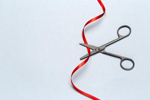 Feierliche eröffnung mit einer schere und einem roten band auf einem grauen dargestellt Premium Fotos