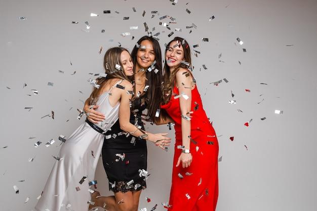 Feiern von jungen freundinnen, die abendkleider tragen, die unter silbernem konfetti auf feiertagsfeier auf grauem hintergrund umarmen Premium Fotos