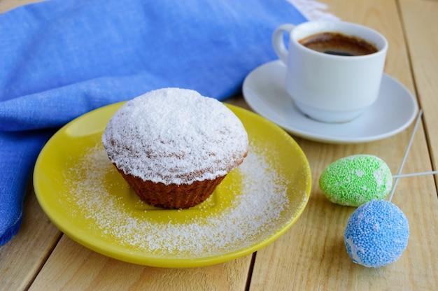 Feiertags-cupcakes-muffins des puderzuckers auf einem hölzernen hintergrund und einer tasse kaffee. Premium Fotos