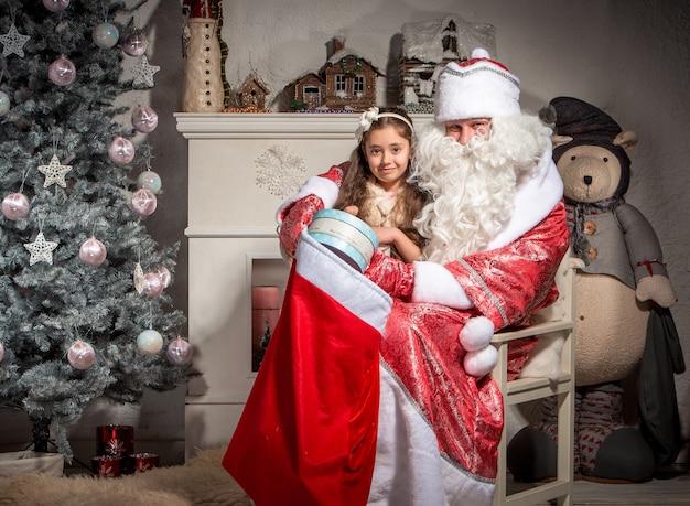Feiertags-, feier-, kindheits- und personenkonzept - lächelndes kleines mädchen mit weihnachtsmann über weihnachtsbaumhintergrund Kostenlose Fotos