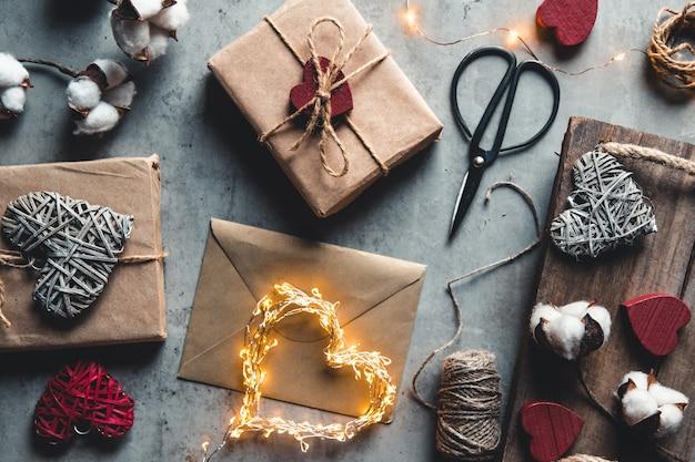 Feiertags-, personen- und feierkonzept - nahaufnahme der frau, die valentinsgeschenke verziert Premium Fotos