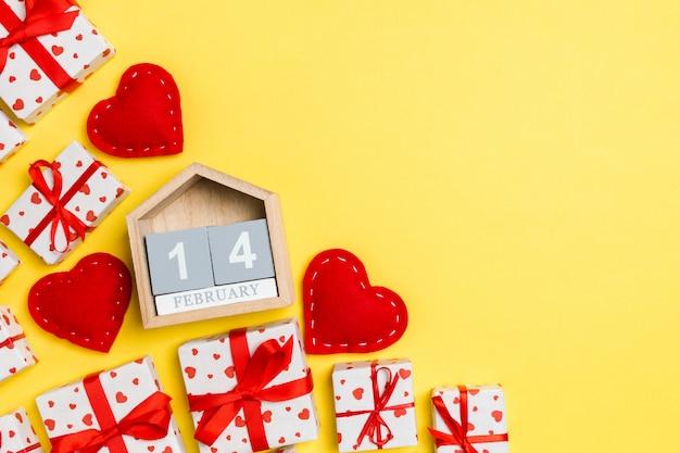 Feiertagszusammensetzung von geschenkboxen, von hölzernem kalender und von roten textilherzen auf tabelle mit leerem raum für ihr design. der vierzehnte februar. draufsicht von Premium Fotos