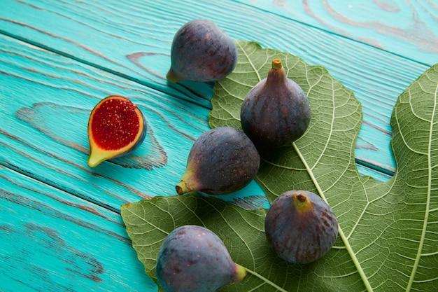 Feigen rohe geschnittene früchte und feigenbaumblätter auf blau Premium Fotos