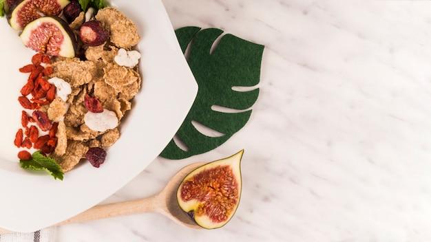 Feigenfruchtscheibe auf hölzernem schöpflöffel nahe geschmackvollem lebensmittel und gefälschtem monstera blatt über küchenarbeitsplatte Kostenlose Fotos