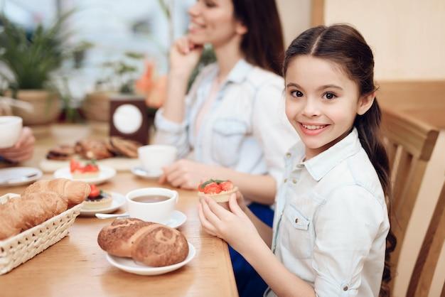Feine glückliche familie, die kuchen in der cafeteria isst. Premium Fotos