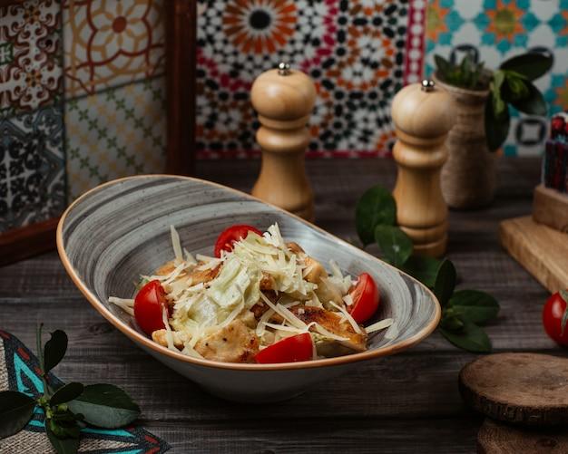 Feiner caesarsalat mit fein gehacktem parmesan und süßkirschen in einer rustikalen schüssel Kostenlose Fotos