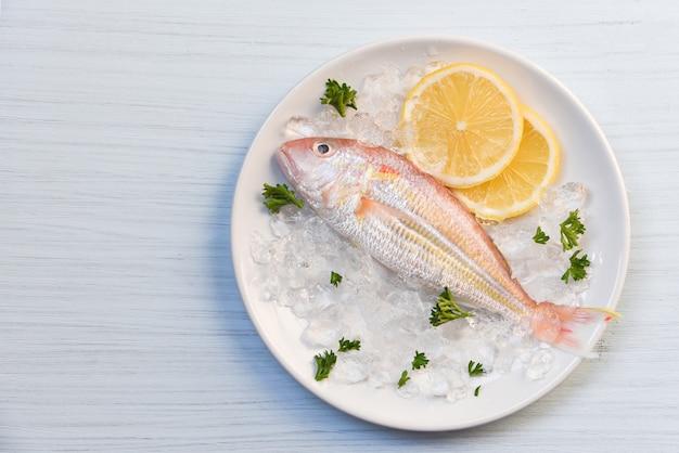 Feinschmeckerische frische fische des meeresfrüchtefischplatten-ozeans auf eiszitronenpetersilie auf weißer plattentabelle Premium Fotos