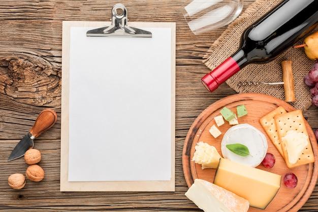 Feinschmeckerische käsezusammenstellung der draufsicht mit weinglas und leerem notizblock Kostenlose Fotos