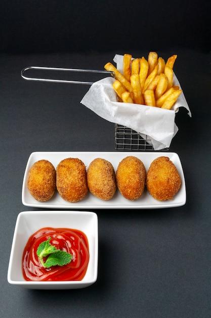 Feinschmeckerische kroketten mit chips auf dunklem hintergrund Premium Fotos