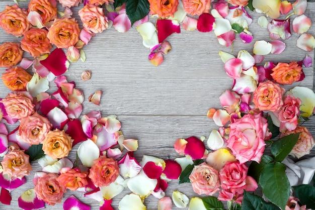 Feld das herz, das von den rosafarbenen blumen gemacht wird, auf hölzernem hintergrund für valentinsgrußtag. Premium Fotos
