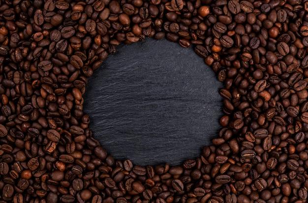 Feld gemacht von den röstkaffeebohnen auf schwarzer tabelle, draufsicht Premium Fotos