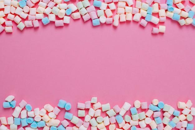 Feld gemacht von den weißen und rosa süßen eibischsüßigkeiten mit kopienraum auf einem rosa hintergrund. Premium Fotos