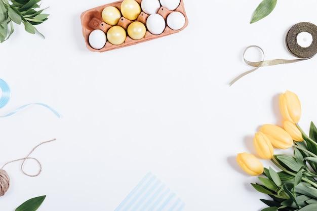 Feld von ostereiern, von gelben blumen, von kästen geschenken und von bändern Premium Fotos
