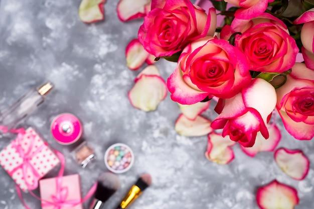 Feld von schönen rosen mit kosmetik auf grauem beton Premium Fotos